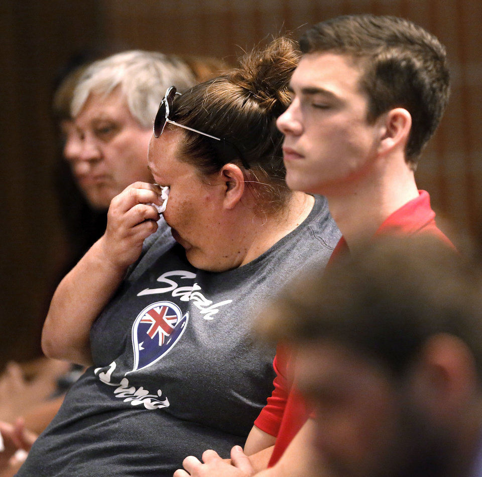 Photo - A woman dabs tears with a tissue during a memorial service for 22-year-old Australian collegiate baseball player Christopher Lane on Saturday, Aug. 24, 2013 in Oklahoma City. Lane was shot in the back and killed last week as he was jogging in an affluent neighborhood in Duncan, in south-central Oklahoma. (AP Photo/The Oklahoman, Jim Beckel) LOCAL STATIONS OUT (KFOR, KOCO, KWTV, KOKH, KAUT OUT); LOCAL WEBSITES OUT; LOCAL PRINT OUT (EDMOND SUN OUT, OKLAHOMA GAZETTE OUT) TABLOIDS OUT ORG XMIT: OKOKL105