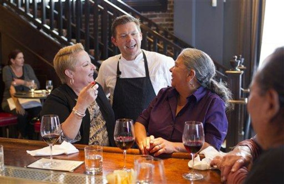 In this photo taken Monday, Oct. 29, 2012, chef Tyler Florence visits with customers at his Wayfare Tavern in San Francisco. (AP Photo/Eric Risberg)
