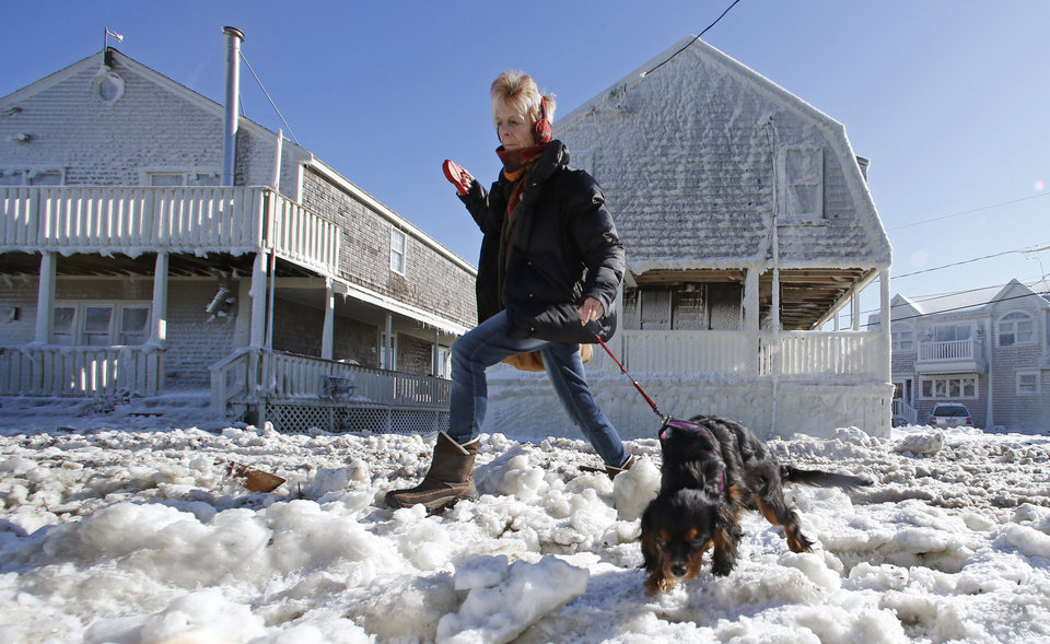 Marj Bates and her dog Simon walk past houses and a street coated with frozen sea water as they walk down Rebecca Road in Scituate, Mass., Sunday, Feb. 10, 2013. The coastal town was hit with a storm surge during a fierce winter storm. More than 650,000 homes and businesses were left without electricity. (AP Photo/Charles Krupa)