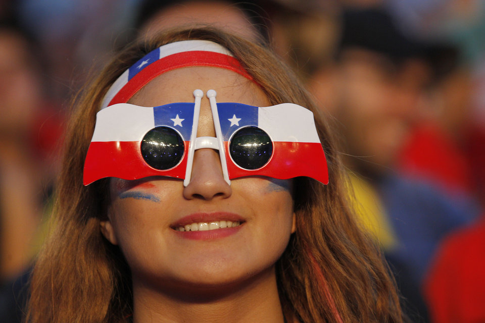 Photo - A soccer fan sports a pair of Chilean flag sunglasses and headband, as she watches a live broadcast of the group B World Cup match between Chile and Spain, inside the FIFA Fan Fest area on Copacabana beach, in Rio de Janeiro, Brazil, Wednesday, June 18, 2014. Chile defeated Spain, the defending champs, 2-0. (AP Photo/Leo Correa)