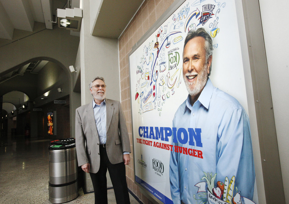 The Regional Food Bank of Oklahoma is one of six nonprofit agencies to be featured in Chesapeake Energy Corp.'s Cheering for Champions campaign. Executive Director Rodney Bivens stands near a sign bearing his picture Wednesday at Chesapeake Energy Arena. Photo by PAUL B. SOUTHERLAND, The Oklahoman