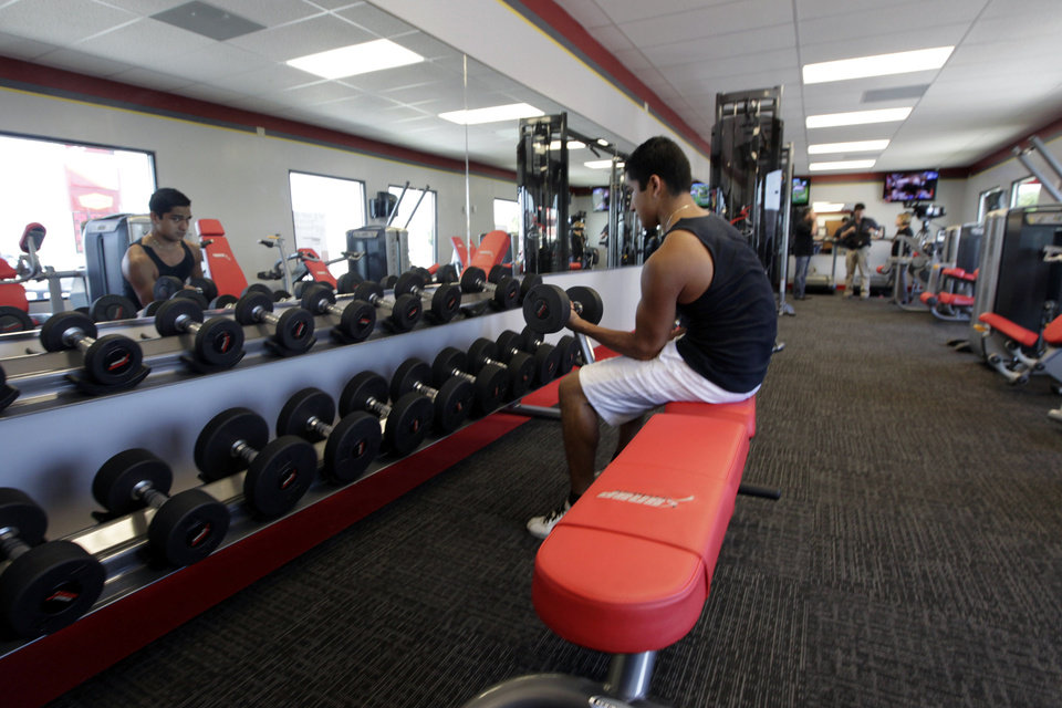 Photo -   ADDS FULL NAME OF GYM - In this June 14, 2012, photo, a customer works out at Snap Fitness Rolling Strong Gym at a truck stop in Dallas. From trucking companies embracing wellness and weight-loss programs to gyms being installed at truck stops, momentum has picked up in recent years to help those who make their living driving big rigs get into shape. (AP Photo/LM Otero)