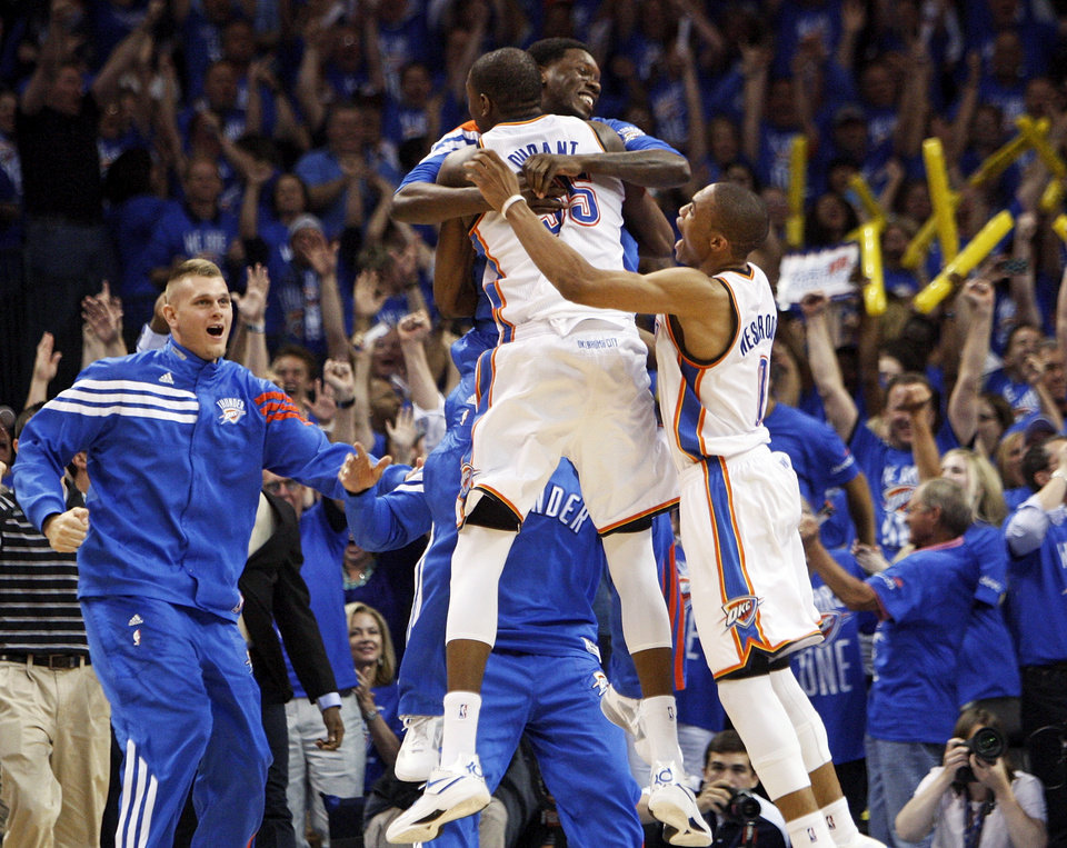 Photo - Oklahoma City's Kevin Durant (35) leaps into the arms of Royal Ivey (7) as Russell Westbrook (0) and Cole Aldrich (45), left, join in the celebration after game one of the first round in the NBA playoffs between the Oklahoma City Thunder and the Dallas Mavericks at Chesapeake Energy Arena in Oklahoma City, Saturday, April 28, 2012. Oklahoma City won, 99-98. Durant made the game-winning shot. Photo by Nate Billings, The Oklahoman