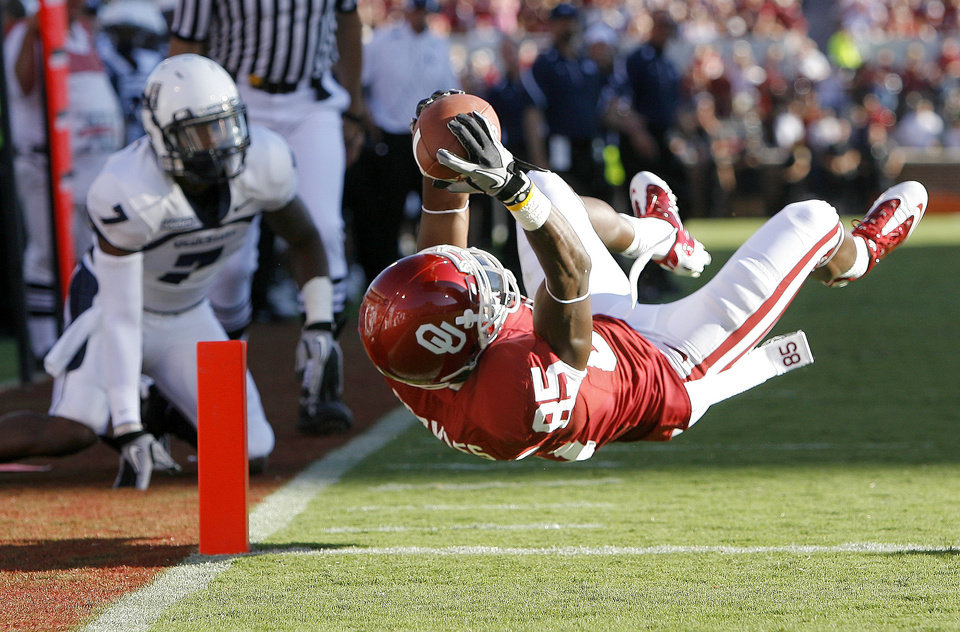 Photo - OU's Ryan Broyles scores a touchdown in front of Utah State's Chris Randle during the first half of the college football game between the University of Oklahoma Sooners (OU) and Utah State University Aggies (USU) at the Gaylord Family-Oklahoma Memorial Stadium on Saturday, Sept. 4, 2010, in Norman, Okla.   Photo by Bryan Terry, The Oklahoman