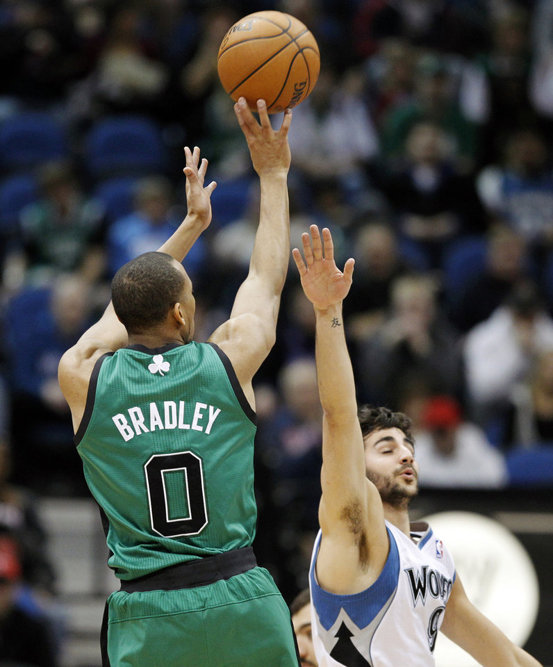 Photo - Boston Celtics guard Avery Bradley (0) shoots a basket over Minnesota Timberwolves guard Ricky Rubio (9), of Spain, during the first half of an NBA basketball game Monday, April 1, 2013, in Minneapolis. (AP Photo/Genevieve Ross)