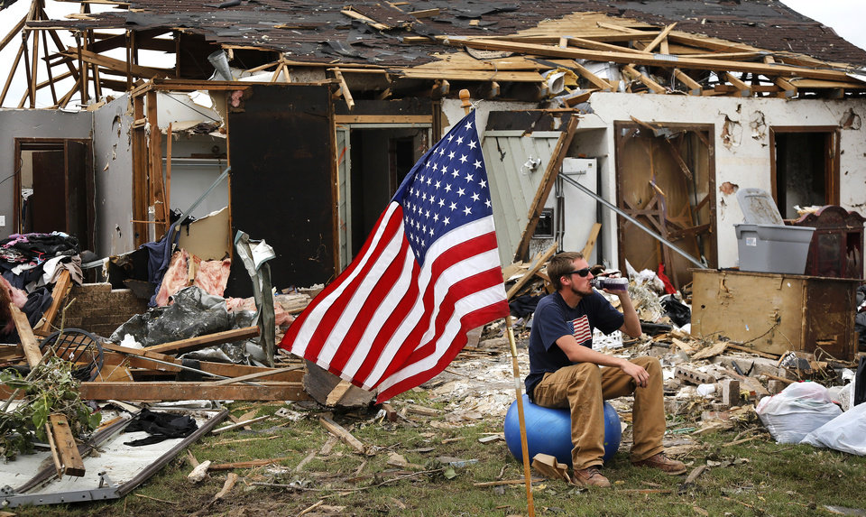 Photo - Dan Wiechmann is a carpenter who came down from his job in Minnesota to help the Moore tornado victims. He sits in the front yard of a heavily damaged home and refreshes himself with liquids during a short break in clean-up efforts Saturday. The volunteers said the American flag was already planted in the yard when they arrived at the house. Volunteers from various parts of the country joined Oklahomans in assisting residents on Saturday,  May 25, 2013, doing whatever was needed to remove debris and salvage items from this neighborhood east of Santa Fe, north of SW 19 Street.  An EF5 tornado leveled many neighborhoods in Moore and southwest Oklahoma City last Monday.   Photo  by Jim Beckel, The Oklahoman.