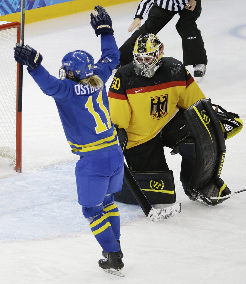 Photo - Goalkeeper Jennifer Harss of Germany looks down as Cecilia Ostberg of Sweden celebrates her goal during the third period of the 2014 Winter Olympics women's ice hockey game at Shayba Arena, Tuesday, Feb. 11, 2014, in Sochi, Russia. (AP Photo/Mark Humphrey)