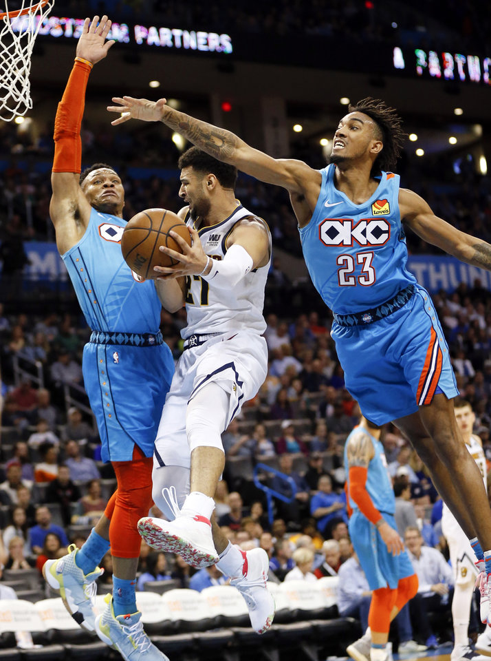 Photo - Denver's Jamal Murray (27) passes between Oklahoma City's Russell Westbrook (0), left, and Terrance Ferguson (23) in the third quarter during an NBA basketball game between the Denver Nuggets and the Oklahoma City Thunder at Chesapeake Energy Arena in Oklahoma City, Friday, March 29, 2019. Denver won 115-105. Photo by Nate Billings, The Oklahoman