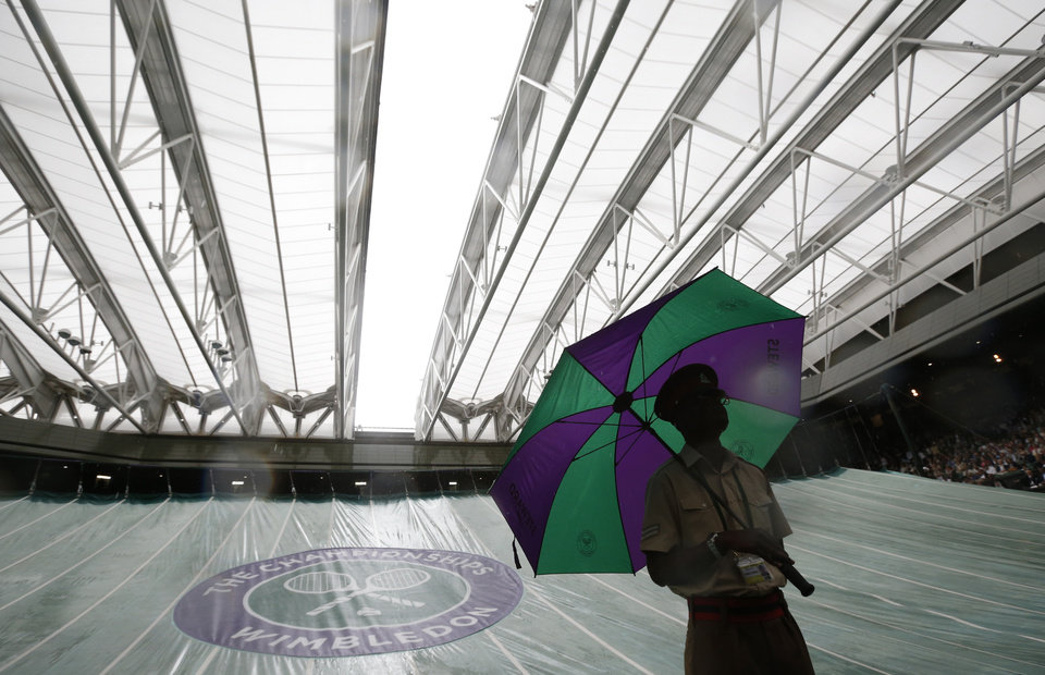 Photo - A British military steward stand with an umbrella as the roof is closed on Centre Court due to rain which led to the suspension of the women's singles match of Eugenie Bouchard of Canada against Alize Cornet of France at the All England Lawn Tennis Championships in Wimbledon, London, Monday, June 30, 2014. (AP Photo/Pavel Golovkin)