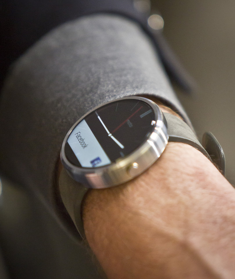 Photo - Steve Sinclair, Motorola's vice president of product management, shows the new Moto 360 circular smartwatch, the company's first, during an interview, Wednesday Aug. 27, 2014 in New York.  (AP Photo/Bebeto Matthews)