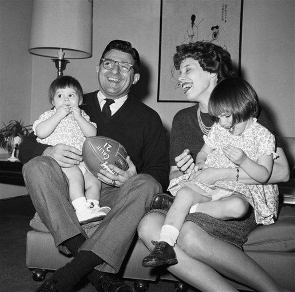 Photo - Joe Paterno, new head football coach at Penn State, left, poses with his two-year-old daughter Diana Lynne Paterno, right on mothers lap, his wife Suzanne Paterno and their one-year-old daughter Mary Kathryn Paterno, on fathers lap, in his home following the announcement, Feb. 19, 1966, University Park, Pa. (AP Photo/Paul Vathis)