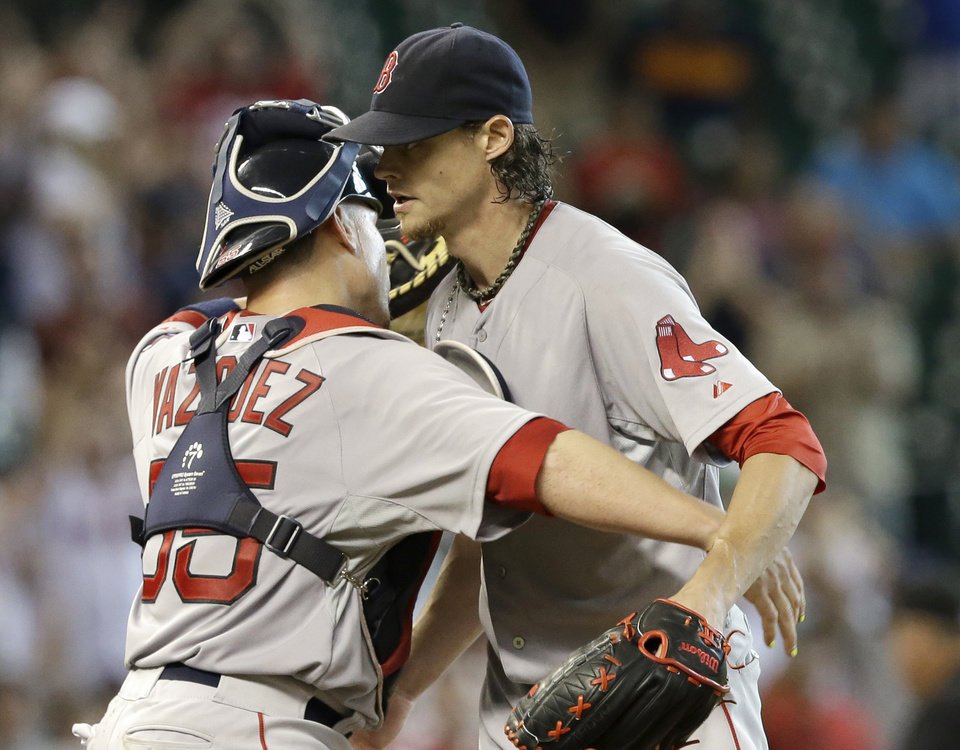 Photo - Boston Red Sox catcher Christian Vazquez, left, hugs starting pitcher Clay Buchholz, right, after beating the Houston Astros 11-0 in a baseball game Sunday, July 13, 2014, in Houston. Buchholz pitched a complete-game shut-out only giving up three hits. (AP Photo/Pat Sullivan)