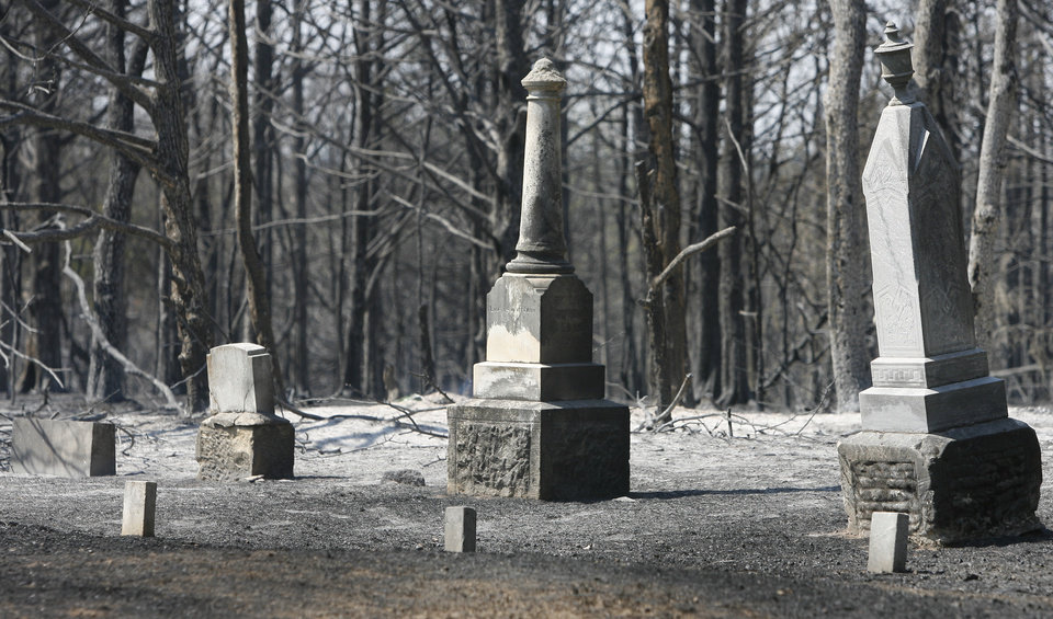 Photo - Grave markers stand in the center of the charred Wright's Cemetery after Tuesdays wildfires swept through the area in Oklahoma City , Wednesday, August 31, 2011. Photo by Steve Gooch, The Oklahoman