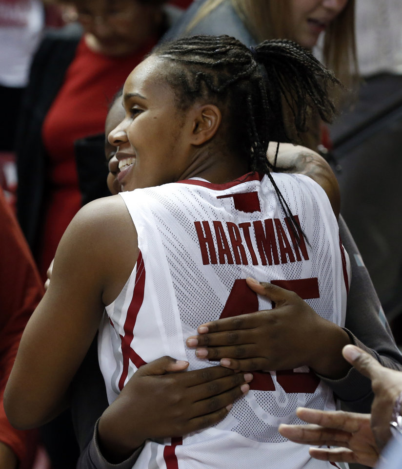 Photo - Senior Jasmine Hartman (45) gets a hug from family members at the Senior Day ceremony after the University of Oklahoma Sooners (OU) defeated the Kansas Jayhawks 85-77 in NCAA, women's college basketball at The Lloyd Noble Center on Saturday, March 2, 2013  in Norman, Okla. Photo by Steve Sisney, The Oklahoman
