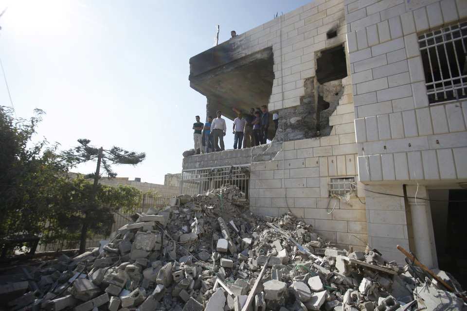 Photo - Palestinians stand in what is left of the home of Amer Abu Aisheh, one of three Palestinians identified by Israel as suspects in the killing of three Israeli teenagers, after it was demolished by the Israeli army in the West Bank city of Hebron, Monday, Aug. 18 , 2014. (AP Photo/Nasser Shiyoukhi)