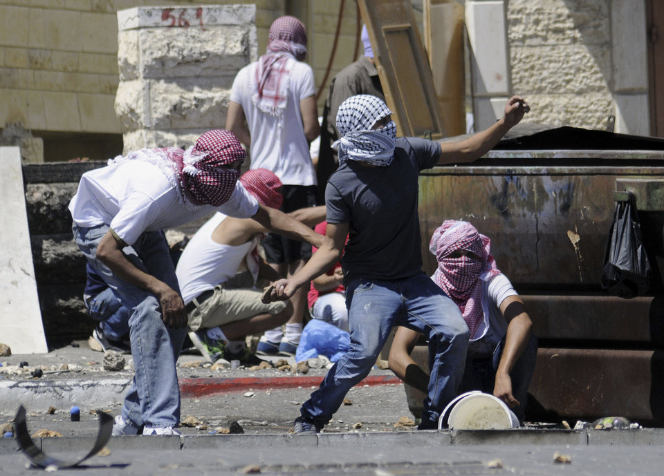 Photo - Palestinians throw stones during clashes with Israeli border police in Jerusalem on Wednesday, July 2, 2014. The suspected abduction of an Arab teen followed by the discovery of a body in Jerusalem on on Wednesday ignited clashes between Israeli police and stone-throwing Palestinians, who saw it as a revenge attack for the killing of three Israeli teens in the West Bank. (AP Photo/Mahmoud Illean)