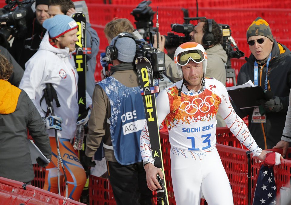 Photo - Gold medal winner Norway's Kjetil Jansrud, left, is interviewed in the finish area as joint bronze medal winner United States' Bode Miller walks away in tears after his television interview at the Sochi 2014 Winter Olympics, Sunday, Feb. 16, 2014, in Krasnaya Polyana, Russia. (AP Photo/Christophe Ena)