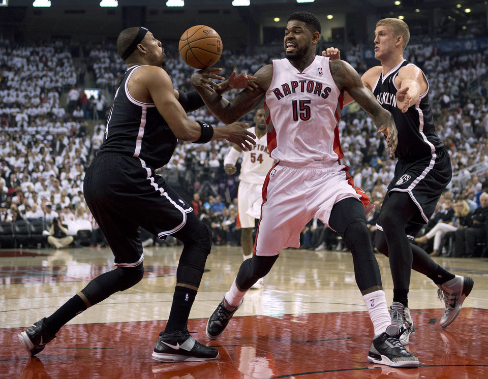 Photo - Toronto Raptors forward Amir Johnson (15) works between Brooklyn Nets forwards Paul Pierce, left, and Mason Plumlee during the first half of Game 2 in an NBA basketball first-round playoff series, Tuesday, April 22, 2014, in Toronto. (AP Photo/The Canadian Press, Frank Gunn)
