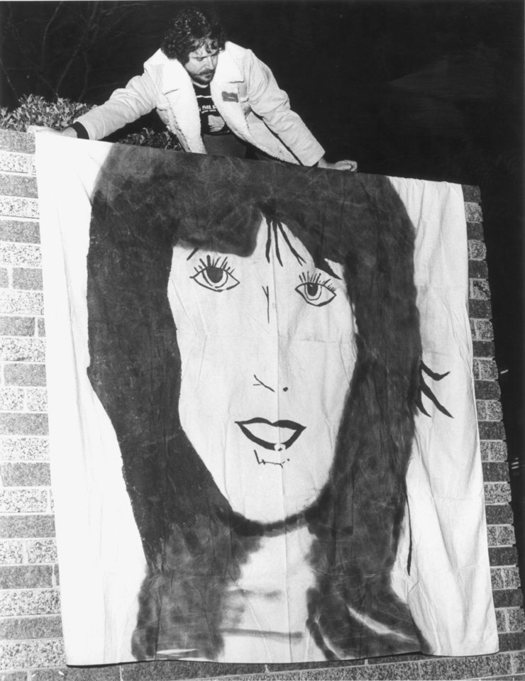 Photo - Jack Smyth, OKC, hangs a portrait of Karen Silkwood during a rally at Kerr Park commemorating the fifth anniversary of Silkwood's death in this Nov 13, 1979 photo. Karen Silkwood, Kerr McGee employee that worked at the plutonium plant near Cresent and the Cimmaron River.
