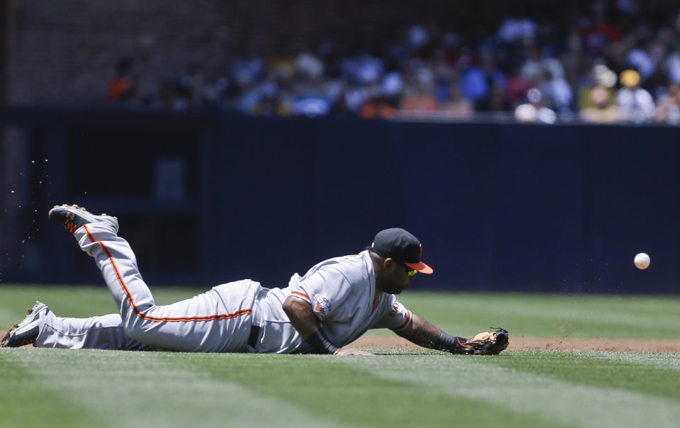 Photo - San Francisco Giants third baseman Pablo Sandoval can't make the diving stop on a single by San Diego Padres' Everth Cabrera in the first inning of a baseball game in San Diego, Sunday, July 14, 2013. (AP Photo/Lenny Ignelzi)