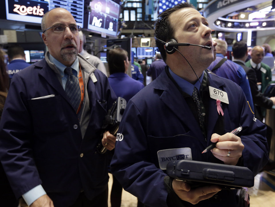 Photo - Trader Robert Vella, right, works on the floor of the New York Stock Exchange Tuesday, Feb. 5, 2013. Stocks are turning higher in early trading on Wall Street following a spike in home prices and strong earnings reports from Kellogg and other U.S. companies. (AP Photo/Richard Drew)