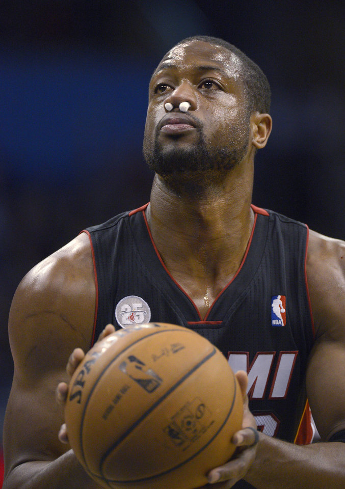 Miami Heat guard Dwyane Wade sets up for a foul shot with plugs in his nose, after receiving an elbow to the face while taking a shot, during the first half of an NBA basketball game against the Orlando Magic in Orlando, Fla., Monday, Dec. 31, 2012. (AP Photo/Phelan M. Ebenhack)