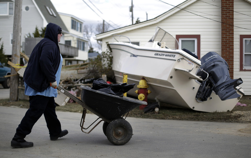 Photo -   Alec Cafone hauls a wheelbarrow containing debris from Superstorm Sandy that damaged the home of Mike Cafone, his grandfather, as he passes a boat that rested against a neighboring house on Cedar Bonnet Island, N.J., Saturday, Nov. 3, 2012. (AP Photo/Patrick Semansky)