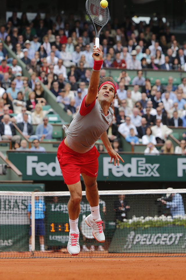 Photo - Switzerland's Roger Federer returns the ball during the fourth round match of the French Open tennis tournament against Latvia's Ernests Gulbis at the Roland Garros stadium, in Paris, France, Sunday, June 1, 2014. (AP Photo/David Vincent)