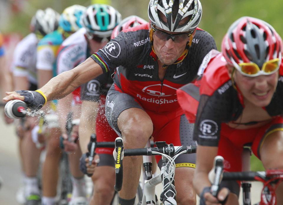 Photo - FILE - In this July 10, 2010, file photo, Lance Armstrong throws out his water bottle in the last kilometers of the climb toward Station les Rousses, France, during the seventh stage of the Tour de France cycling race. The New York Times reported Friday, Jan. 4, 2013, that Armstrong, who has strongly denied the doping charges that led to him being stripped of his seven Tour de France titles, has told associates he is considering admitting to the use of performance-enhancing drugs. Armstrong attorney Tim Herman denied that Armstrong has reached out to USADA chief executive Travis Tygart and David Howman, director general of the World Anti-Doping Agency. (AP Photo/Bas Czerwinski, File)