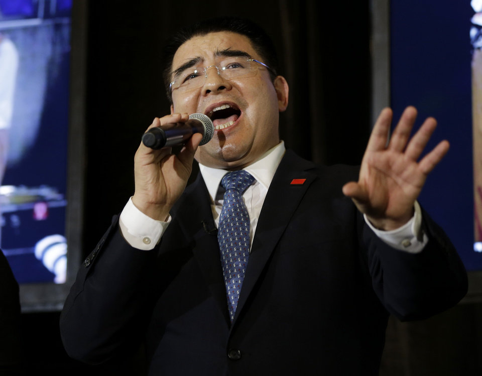 Photo - Recycling magnate Chen Guangbiao sings to the media and his guests from the  New York City Rescue Mission at The Loeb Boathouse restaurant in New York, Wednesday, June 25, 2014. The Chinese tycoon known for his sometimes eccentric gestures served up a fancy lunch Wednesday to hundreds of homeless New Yorkers at a Central Park restaurant and serenaded them with