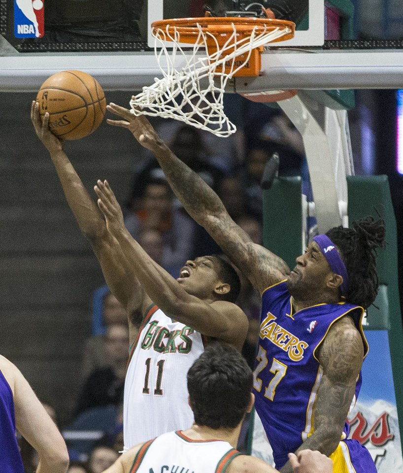 Photo - Milwaukee Bucks' Brandon Knight shoots a reverse lay-up as Los Angeles Lakers' Jordan Hill defends during the first half of an NBA basketball game Thursday, March 27, 2014, in Milwaukee. (AP Photo/Tom Lynn)