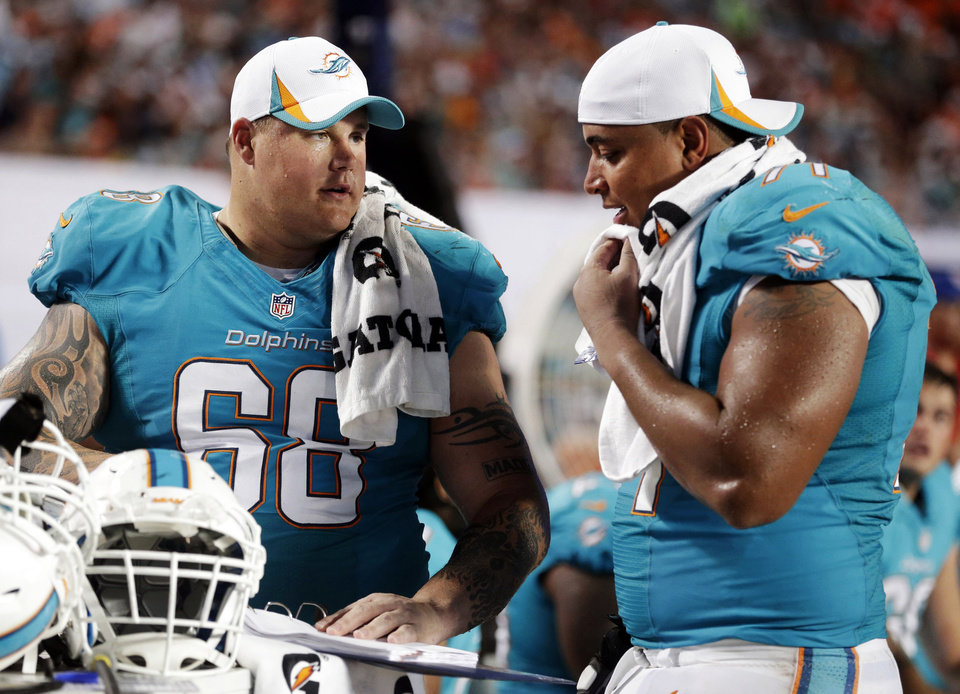 Photo - FILE - In this Aug. 24, 2013, file photo, Miami Dolphins guard Richie Incognito (68) and tackle Jonathan Martin (71) look over plays during an NFL preseason football game against the Tampa Bay Buccaneers in Miami Gardens, Fla. Martin was subjected to