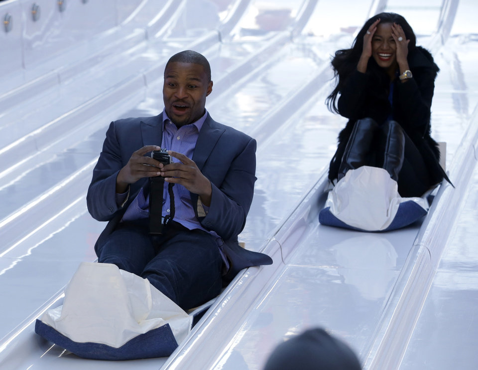 Photo - Atlanta Falcons defensive end Osi Umenyiora, left, and his fiancee, Miss Universe 2011 Leila Lopes, right, slide down the toboggan slide during Super Bowl Boulevard festivities Wednesday, Jan. 29, 2014, in New York. The Seattle Seahawks are scheduled to play the Denver Broncos in the NFL Super Bowl XLVIII football game on Sunday, Feb. 2, in East Rutherford, N.J. (AP Photo/Julio Cortez)