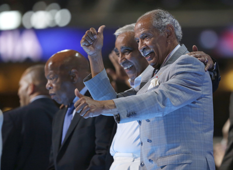 Photo - Members of Congressional Black Caucus Rep. John Lewis, D-Ga., left, Rep. Charles B. Rangel, D-N.Y., and Rep. John Conyers, D-Mich., applaud from the stage during the third day session of the Democratic National Convention in Philadelphia, Wednesday, July 27, 2016. (AP Photo/Carolyn Kaster)