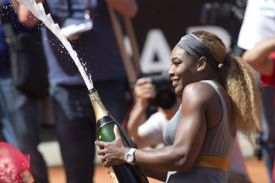 Photo - Serena Williams sprays sparkling wine as she celebrates after winning the final against Italy's Sara Errani at the Italian Open tennis tournament, in Rome, Sunday, May 18, 2014. Serena Williams kept the crowd from being a factor in a 6-3, 6-0 victory over 10th-seeded Sara Errani to win the Italian Open for the third time Sunday. (AP Photo/Andrew Medichini)