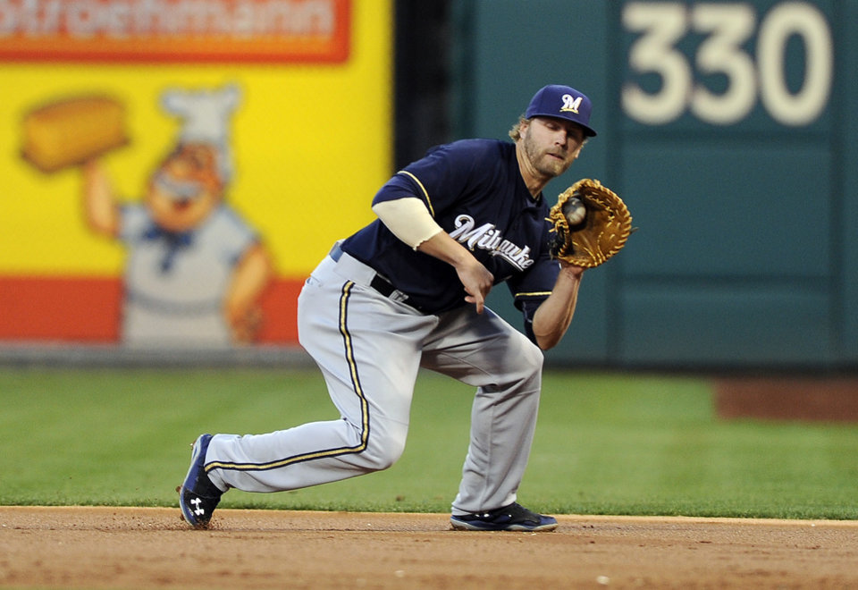 Photo - Milwaukee Brewers first baseman Mark Reynolds fields a grounder by Philadelphia Phillies' Chase Utley in the first inning of a baseball game Thursday, April 10, 2014, in Philadelphia. Reynolds stepped on the base for the out. (AP Photo/Michael Perez)
