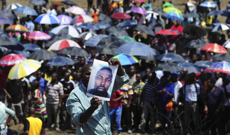 A man holds an image of an un-named alleged victim of the recent mining violence during a demonstration in Rustenburg, South Africa, Saturday Oct. 6 2012. A leader for striking miners at Anglo American Platinum mines in South Africa said they would make it difficult for the company to hire new miners after the company fired 12,000 striking workers earlier this week. (AP Photo)