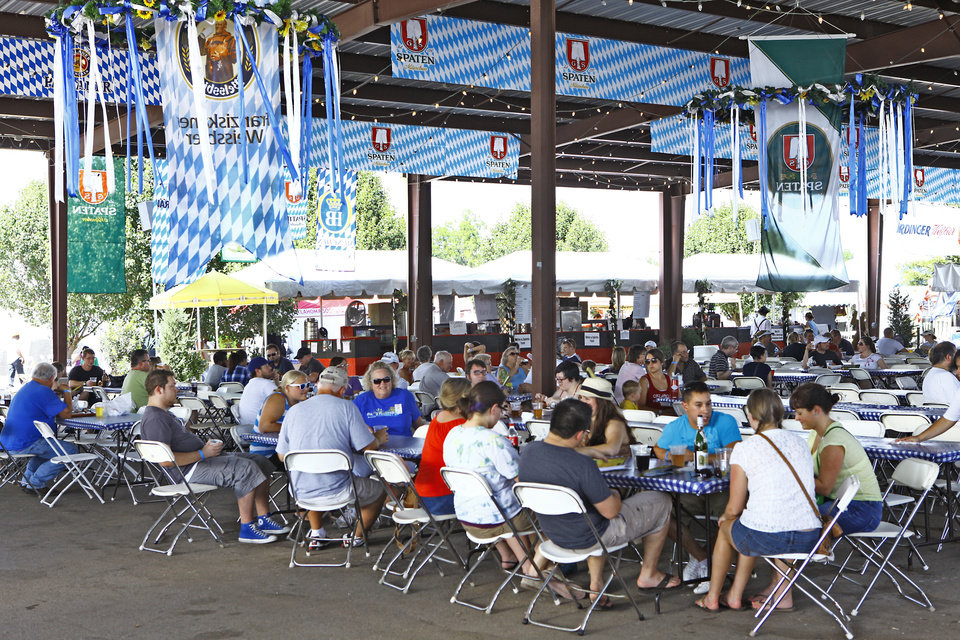 Photo - People enjoy food and beverages under a pavilion during Oktoberfest in the Park in Choctaw on Monday, September 3, 2012. Photo By David McDaniel/The Oklahoman