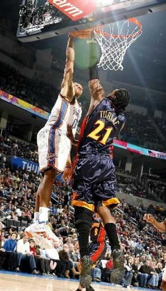 Photo - Oklahoma City's Russell Westbrook puts up a shot despite pressure from Ronny Turiaf during the NBA game between the Oklahoma City Thunder and  Golden  State Warriors, Sunday, 31, 2010, at the Ford Center in Oklahoma City. Photo by Sarah Phipps