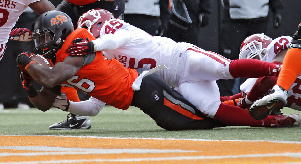 Photo - Oklahoma's Caleb Gastelum (45) stops Oklahoma State's Desmond Roland (26) just short of the goal line during the Bedlam college football game between the Oklahoma State University Cowboys (OSU) and the University of Oklahoma Sooners (OU) at Boone Pickens Stadium in Stillwater, Okla., Saturday, Dec. 7, 2013. Photo by Chris Landsberger, The Oklahoman