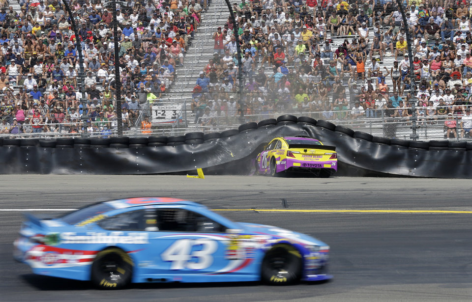Photo - Aric Almirola (43) drives through Turn 1 as Cole Whitt (26) crashes into the tire wall during a NASCAR Sprint Cup Series auto race at Watkins Glen International, Sunday, Aug. 10, 2014, in Watkins Glen, N.Y. (AP Photo/Mel Evans)
