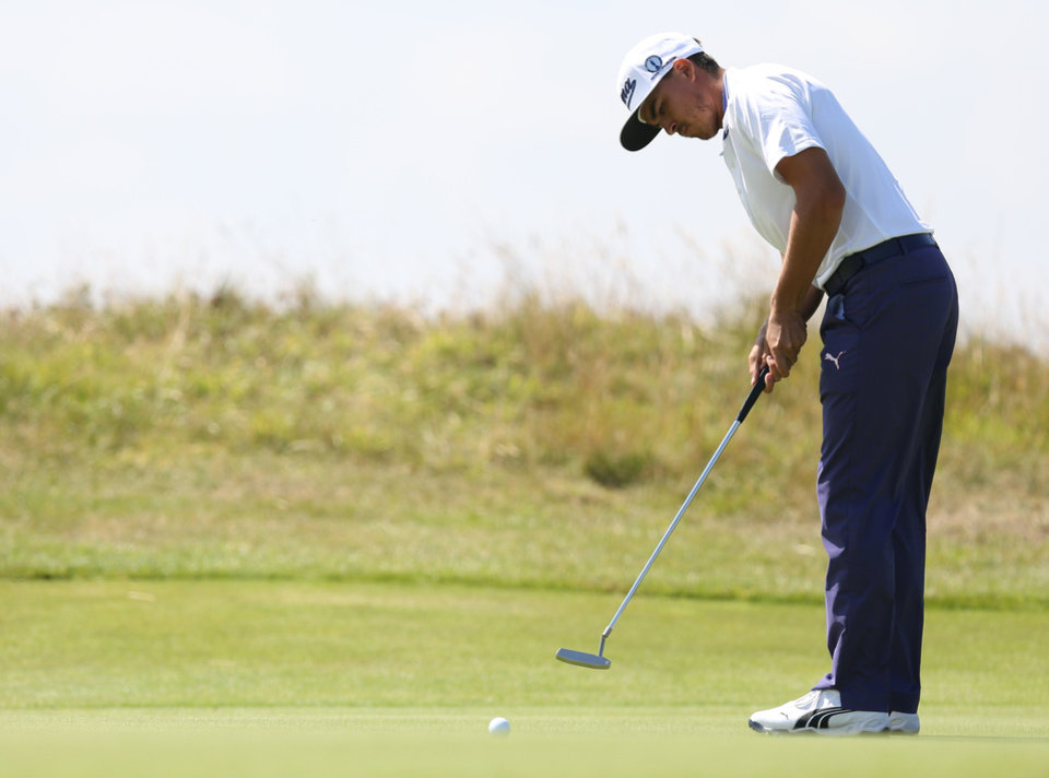 Rickie Fowler of the US putts on the 14th green during the first day of the British Open Golf championship at the Royal Liverpool golf club, Hoylake, England, Thursday July 17, 2014. (AP Photo/Scott Heppell)
