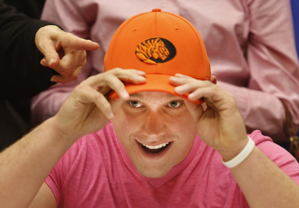 Photo - Westmoore's Josh Morgan puts on his hat after signing to play football for East Central University during a signing ceremony at Westmoore High School in Moore, Wednesday February  06, 2013. Photo By Steve Gooch, The Oklahoman