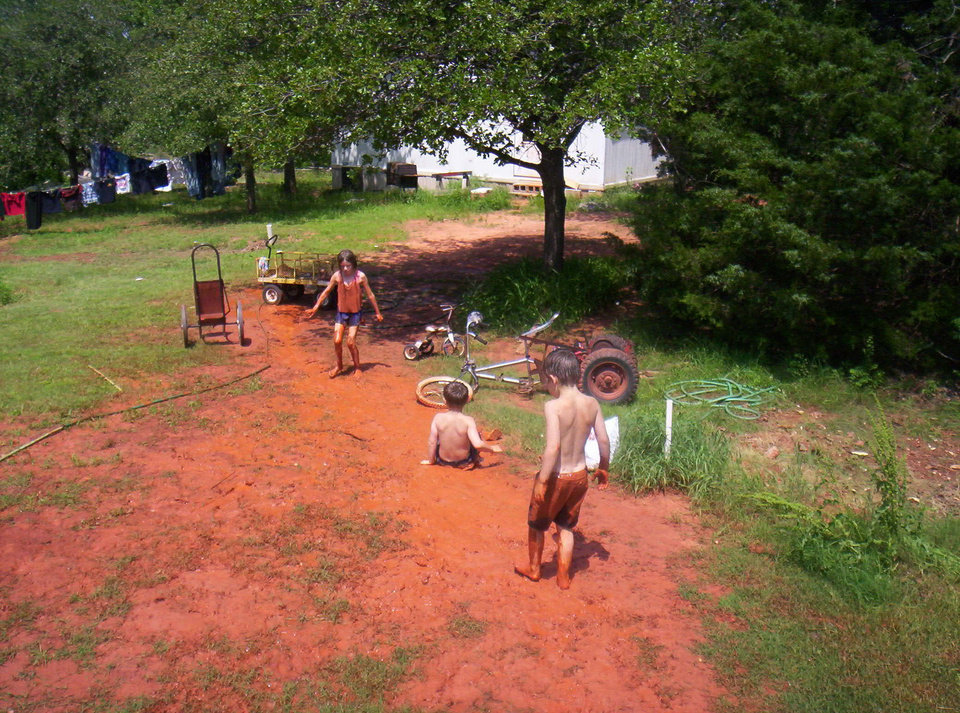 Oklahoma slip and slide. The kids used the water hose to make a mud slide. Charlotte, Charles and Chance.  Guthrie, Ok<br/><b>Community Photo By:</b> Joanna Miller<br/><b>Submitted By:</b> Joanna, Guthrie