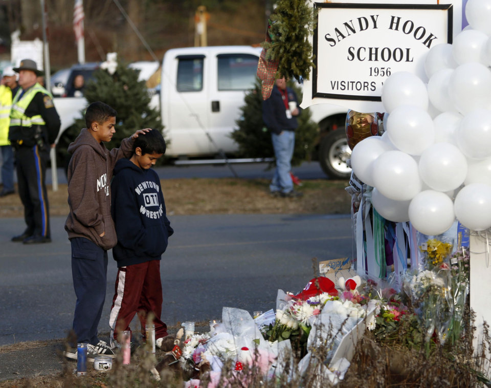 Photo - Brothers Thomas, 13, left, and Steven Leuci, 9, pay their respects at a memorial for shooting victims near Sandy Hook Elementary School, Saturday, Dec. 15, 2012 in Newtown, Conn.  A gunman walked into Sandy Hook Elementary School in Newtown Friday and opened fire, killing 26 people, including 20 children. (AP Photo/Jason DeCrow) ORG XMIT: CTJD114