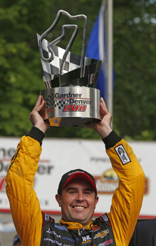 Photo - Brendan Gaughan lifts the trophy in Victory Lane after winning the NASCAR Nationwide series race at Road America in Elkhart Lake, Wis., Saturday, June, 21, 2014.  (AP Photo/Jeffrey Phelps)