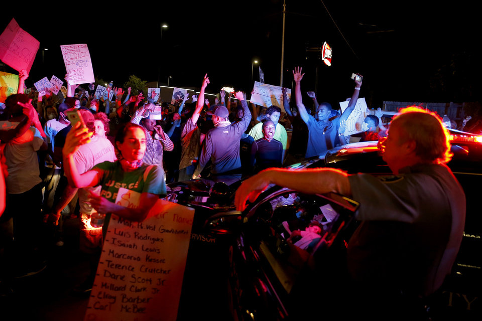 Photo - Protesters surround an Oklahoma City police vehicle on Pennsylvania Avenue in Oklahoma City, Saturday, May 30, 2020. The protest was in response to the death of George Floyd. [Bryan Terry/The Oklahoman]
