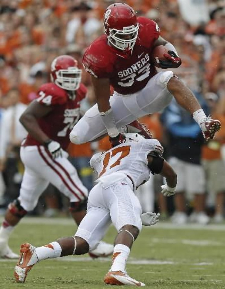 Photo -  OU's Trey Millard (33) leaps over UT's Adrian Phillips (17) during the Red River Rivalry on Saturday, Oct. 13, 2012. Photo by Bryan Terry, The Oklahoman
