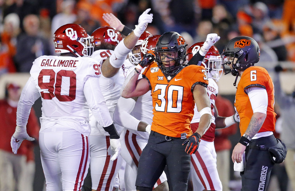 Photo - Oklahoma celebrates a stop as Oklahoma State's Chuba Hubbard (30) and Dru Brown (6) walk off the field in the fourth quarter during the Bedlam college football game between the Oklahoma State Cowboys (OSU) and Oklahoma Sooners (OU) at Boone Pickens Stadium in Stillwater, Okla., Saturday, Nov. 30, 2019. OU won  34-16. [Sarah Phipps/The Oklahoman]
