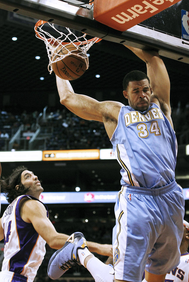 Photo -   Denver Nuggets' JaVale McGee (34) dunks as Phoenix Suns' Luis Scola, of Argentina, watches in the first half during an NBA basketball game on Monday, Nov. 12, 2012, in Phoenix. (AP Photo/Ross D. Franklin)